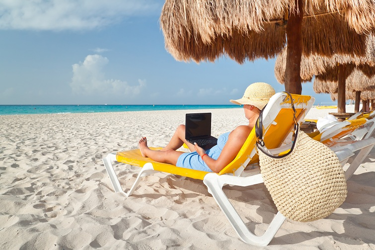 Caribbean Sea: Woman with laptop relaxing on the deckchair