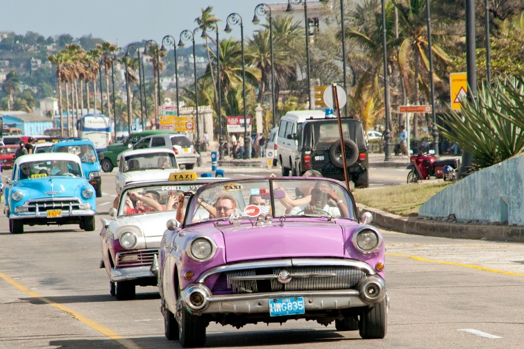 Cuba - Tourists in vintage cars along the Malecon in Havana.