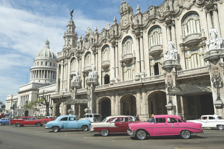 Row of brightly colored vintage American cars stand parked in front of the landmark architecture of the Great Theater of Havana. Photo Credit: ©lazyllama/Shutterstock.com.