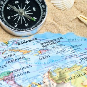 Map of Caribbean on beach with compass. Photo Credit: ©stockWERK/Adobe Stock.