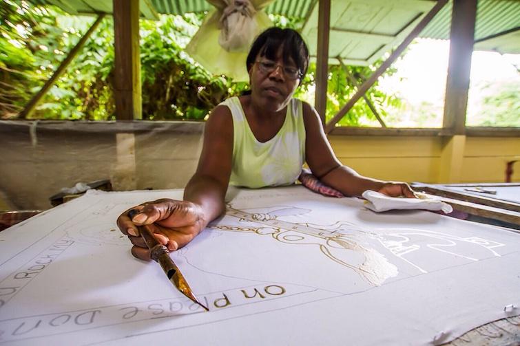 Romney Manor: Caribelle Batik_Patsy using a tjanting, a wax pen to create unique designs.