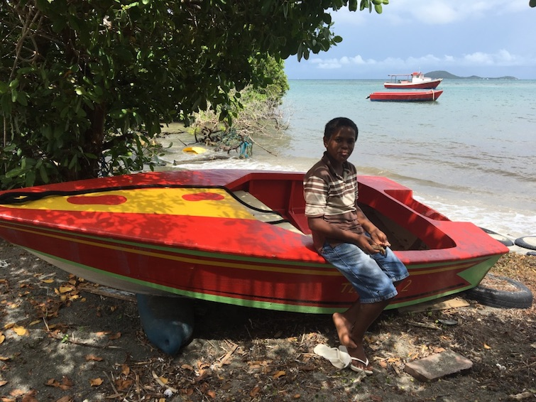 Carriacou: Little boy sitting on small colorful boat.