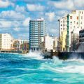 Cuba: Panoramic view of the Havana skyline with waves crashing into the Malecon seawall. Photo Credit: © Kmiragaya / Adobe Stock.