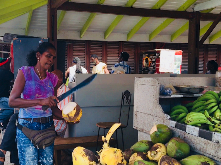 Grenada Spice Market: Coconut Water Stand - Ms Katherine cutting a coconut.