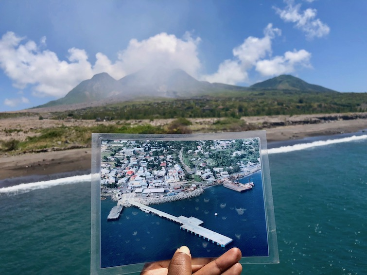 Holding a picture of Plymouth in Montserrat now buried under volcanic ash and mud. Photo Credit: © Ursula Petula Barzey.
